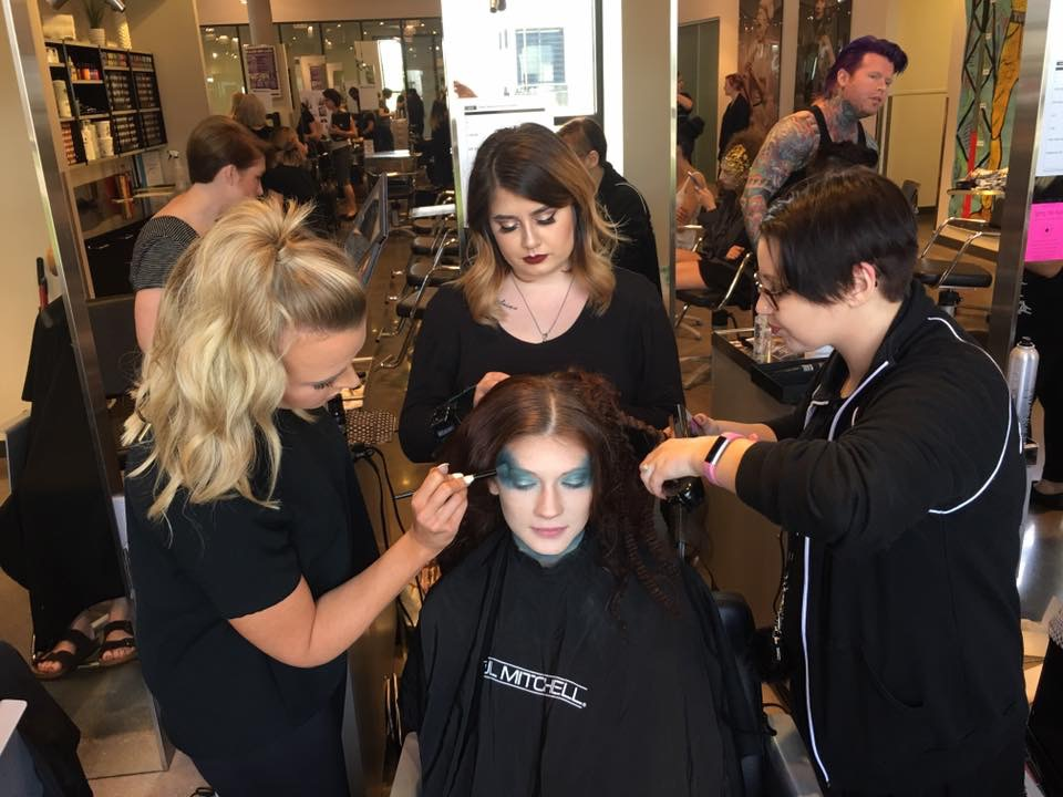 Left to right: Jaclyn Swanson, Morgan Miller, and Brooke Anthony prepare Rianne Ross before the show.