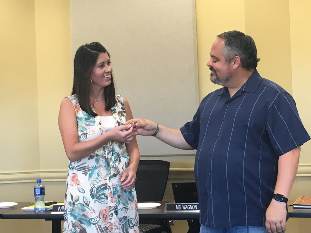 Northwoods principal Laura Hamilton is presented with a Coin of Excellence by Board of Education Chairman Rusty Gunn.