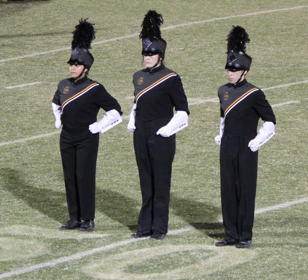 Drum Majors Brandi Sigala, Laura Loomis, and Jake Thompson lead the band onto the field for competition. (Photo: Tristia Watson).