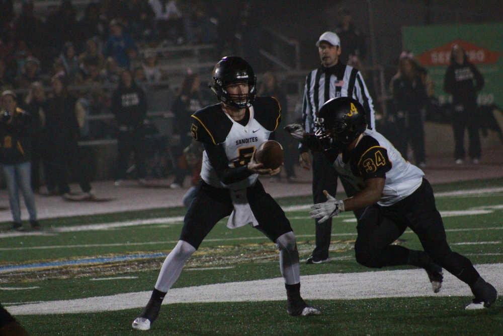 Former Sandite quarterback Hunter Greathouse hands the ball off to Payton Scott in last year's 26-25 victory over No. 1 Muskogee. Scott carried 25 times for 116 yards and a touchdown in that game. (Photo: Scott Emigh).