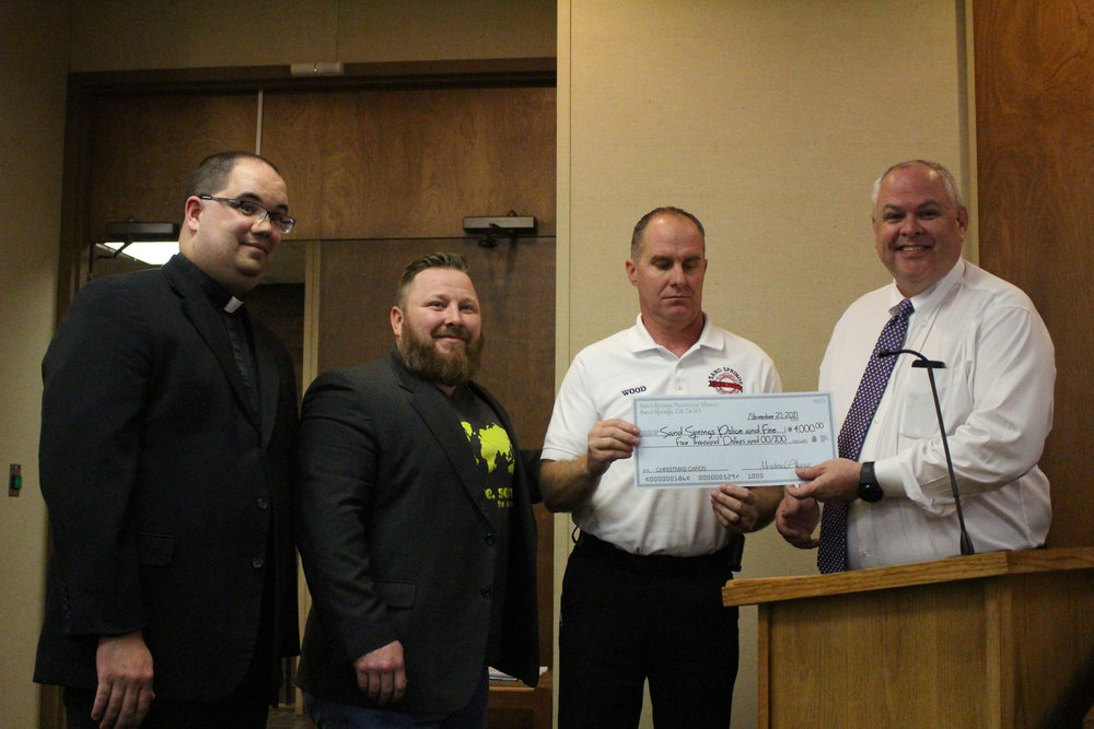 Left to right: Pastors Todd Nance and Steve Allen present Fire Chief Mike Wood and Police Chief Mike Carter with a donation towards Christmas bonuses for the departments.