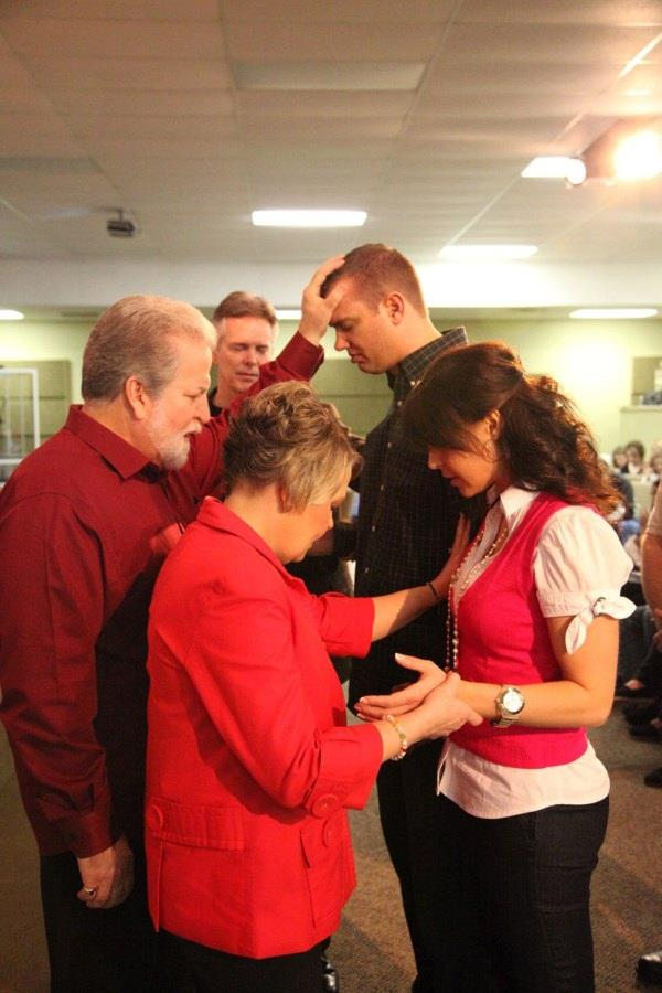 Word of Life founding pastors David and Sharon Emigh pray over current pastors Chad and Sarah Stewart.