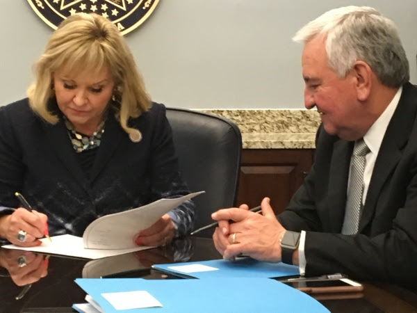 Governor Mary Fallin, with Secretary of State, Education and Workforce Development Dave Lopez watching, on Tuesday signs House Bill 1020XX, the 2018 fiscal year budget bill.