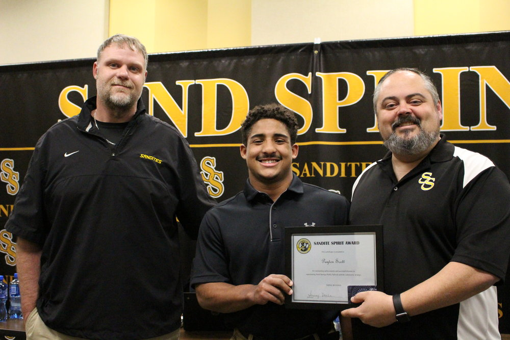 mar. 05, 2018. cphs head football coach Dustin Kinard and board of ed member Rusty Gunn present Payton Scott with a Sandite Spirit Award.