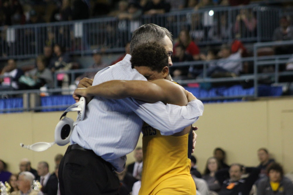 Payton Scott hugs CPHS Head Wrestling Coach Kelly Smith after winning the 2017 State Championship. (Photo: Scott Emigh).