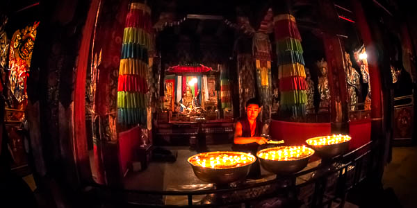 Monk with butter lamps, Samye Monastery, Tibet By Michael Smyth