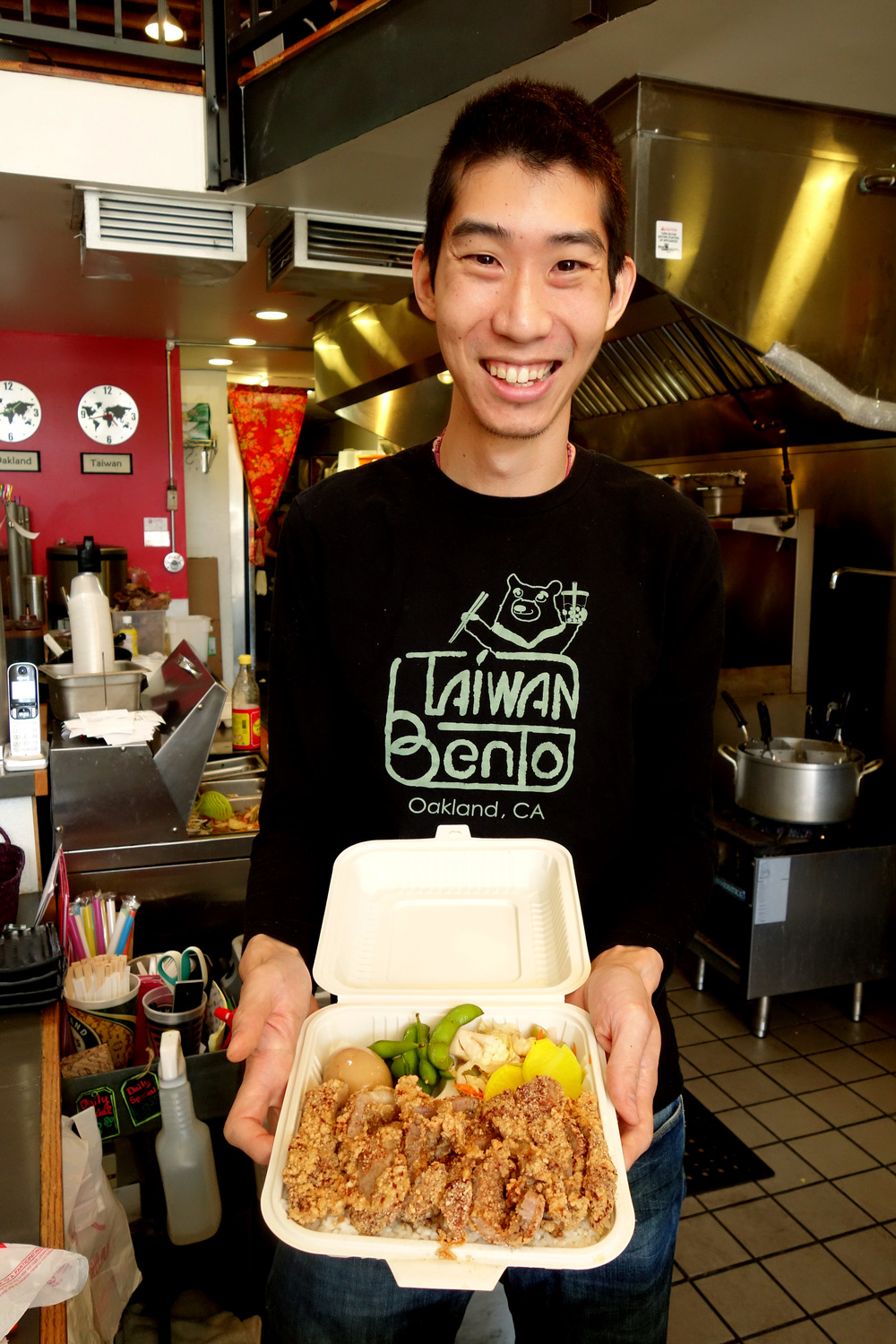 Willy Wang holding their Chicken Bento at Taiwan Bento in Oakland, California. 2016.