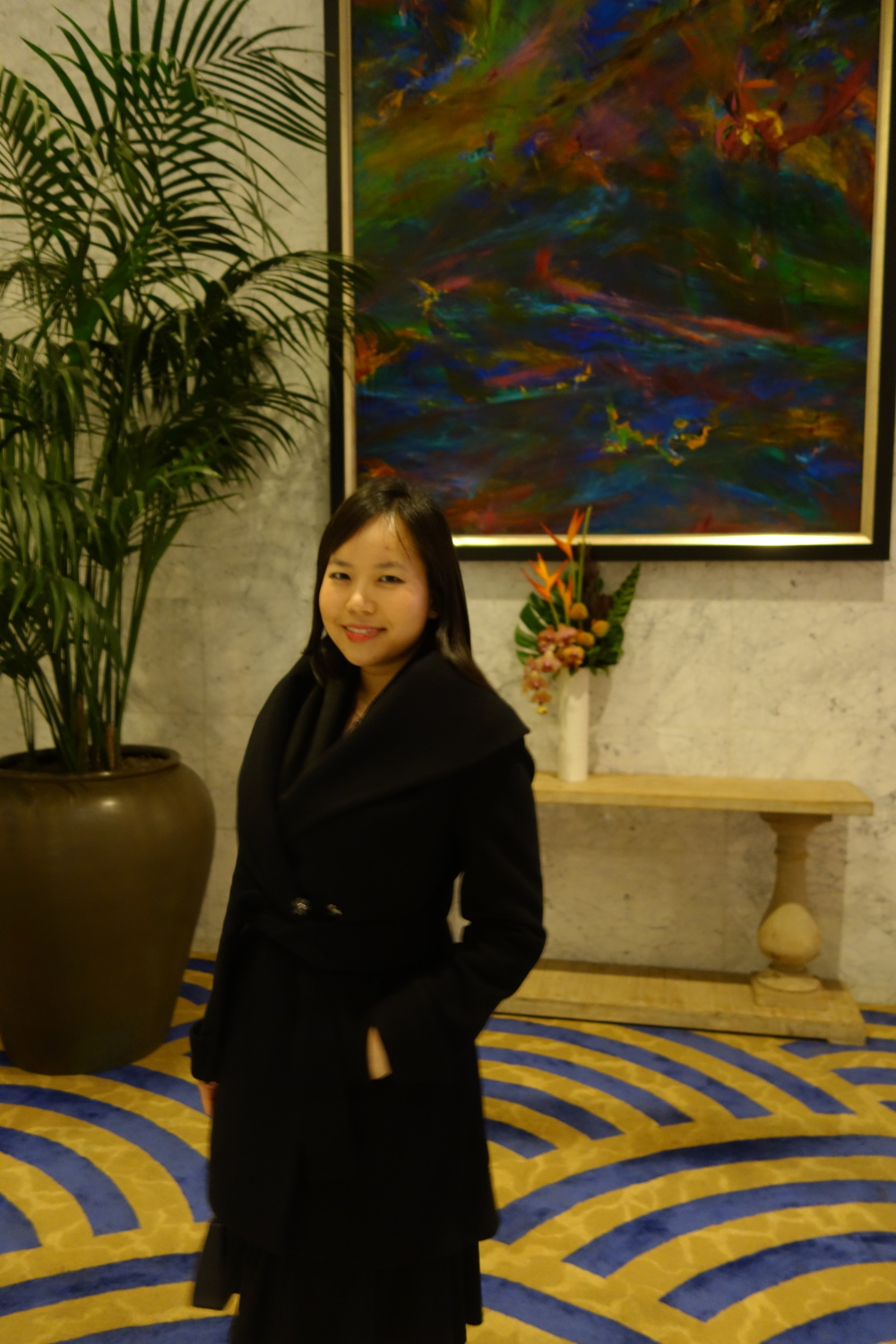 Sandy Leung in front of the large modernist oil painting and bright orange flowers at the Lobby of Hotel Nikko.