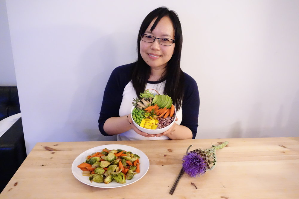 Sandy Leung from SandyByTheBay.com food blog, holding the Vitality Bowl. Maple Glazed Brussels Sprouts (On The Table). Recipes from MeatLess.