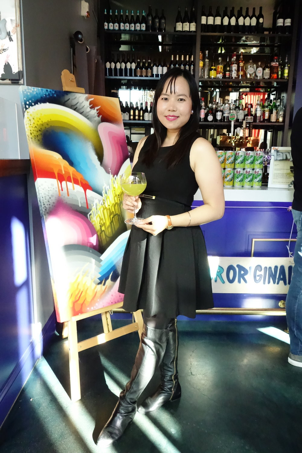 SandyByTheBay.com's Sandy Leung with a custom cocktail by Hansen's & Rooh SF. Artwork by Ricky Watts (Left).