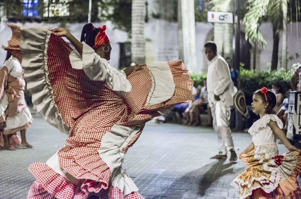 """Woman dances """"Mapalé""""in a square in Cartagena while a little girl tries to emulate her. The Afro-Colombian music and dance is particular to the Pacific and Caribbean coasts of Colombia, but has spread to Central America and as far south as Perú."""