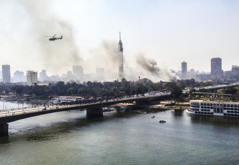 Protesters set the Police Academy Club on fire in Zamalek in Western Cairo, Egypt with flares and Molotov cocktails. Helicopters try to drop water on the flames while protesters block the bridge and set tires ablaze.