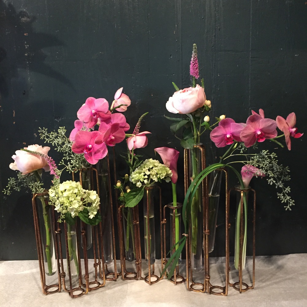 "We find that using traditional ""gardeny"" cut flowers such as garden roses and veronica provide a lovely soft contrast to the smart metal angles of the frame."
