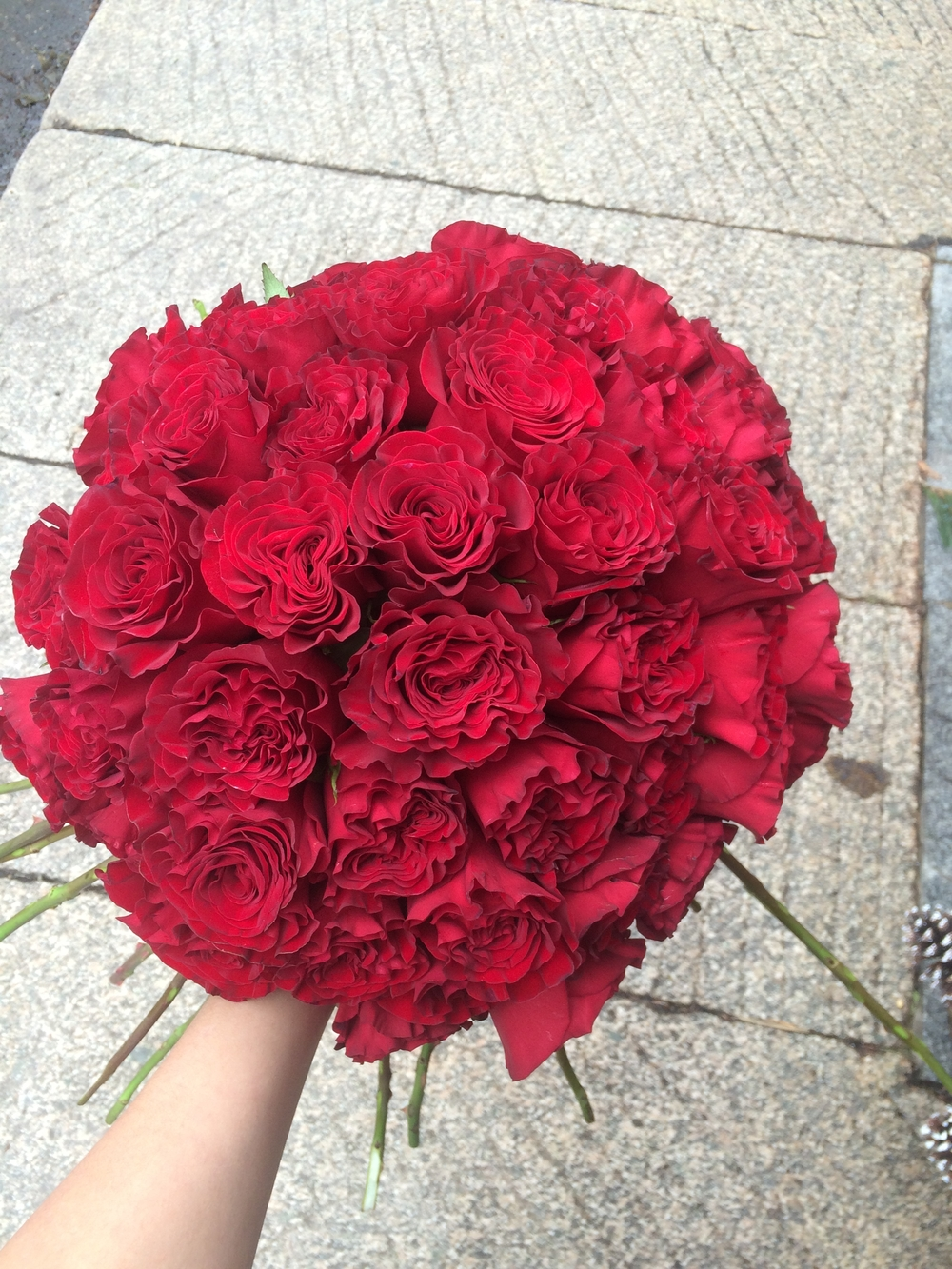 """We start by arranging 50 large red roses in the hand-tied style. This can be very difficult. Especially if you haven't de-thorned the roses! The rose variety we've used here is called """"Heart"""". It has an absolutely irresistible ruffled petal and color."""