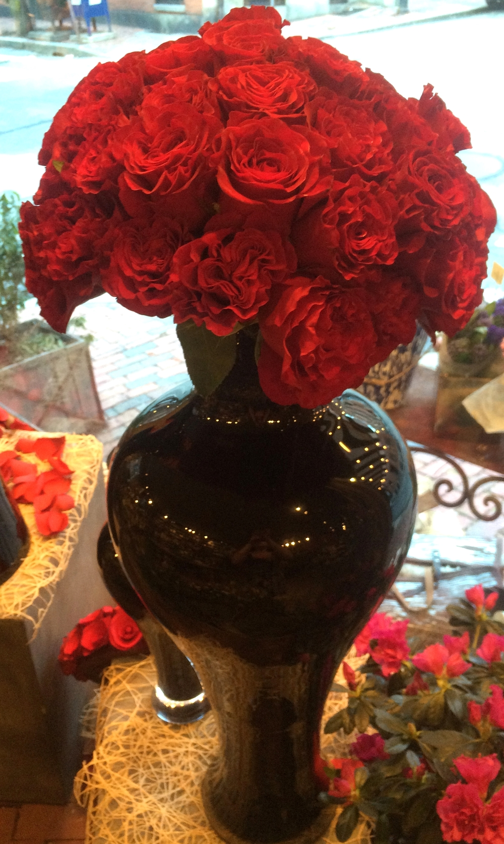 """Here we've placed it in a sleek and modern black glass vase. This style of arranging is known as Pav é-floral or """"head to head""""."""