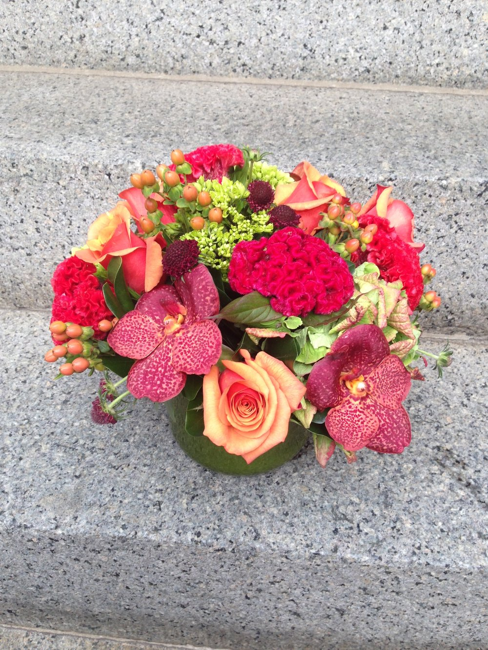 Warmer sunset tones are softened in this arrangement by the celosia flower, which has a fuzzy texture to it.