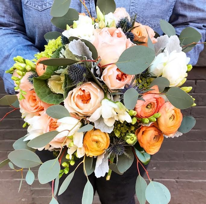 The beautiful bridal bouquet - including ranunculus, garden roses, freesia, thistle, hydrangea, and eucalyptus.