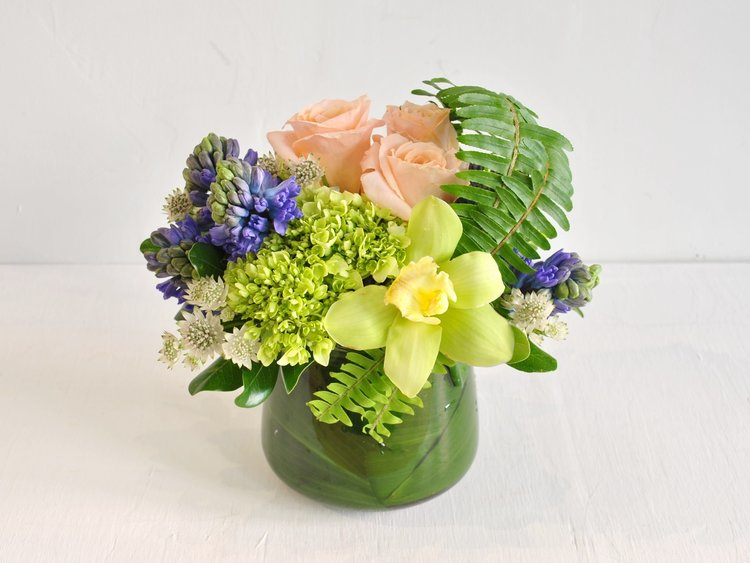 Soft playful tones of blue, peach and green bring about thoughts of the springtime thaw and picnics in a meadow. Fragrant hyacinth, shimmer roses, cream astrantia, chartreuse cymbium. hydrangea and sword ferns are collected in a rounded glass vase.