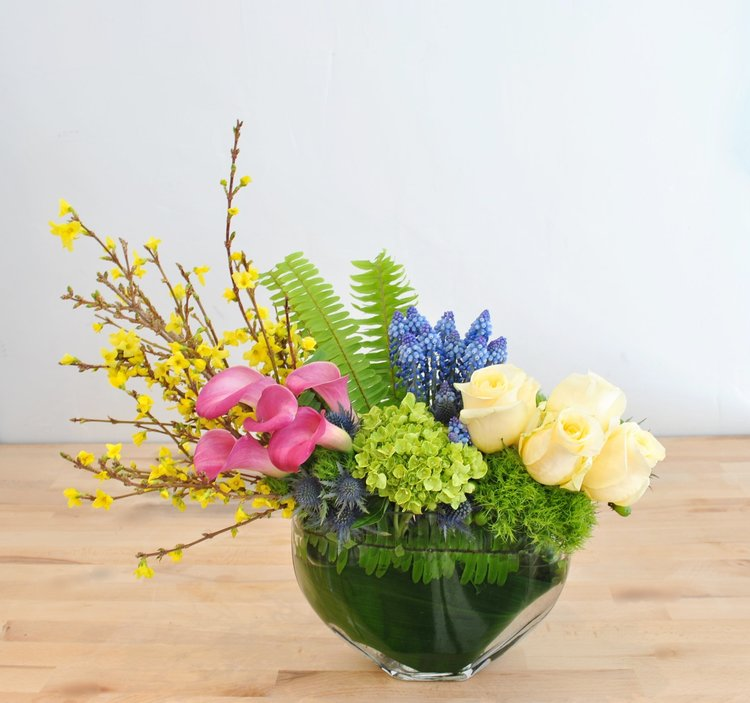 Reminiscent of the first day of spring; colorful clusters of calla lilies, forsythia, muscari and Crème de La Crème roses are complimented by bright green hills of hydrangea and textural thistle in a unique envelope vase.