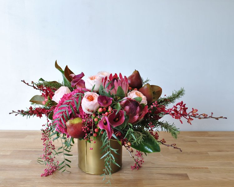 Rhubarb a velvety, sumptuous arrangement in our gold metal pot. Soft peach Juliet garden roses and hypericum berries pop against bold magnolia leaves, seckle pears, hanging pepperberry, exotic Pink Ice protea & James Storeii orchids.
