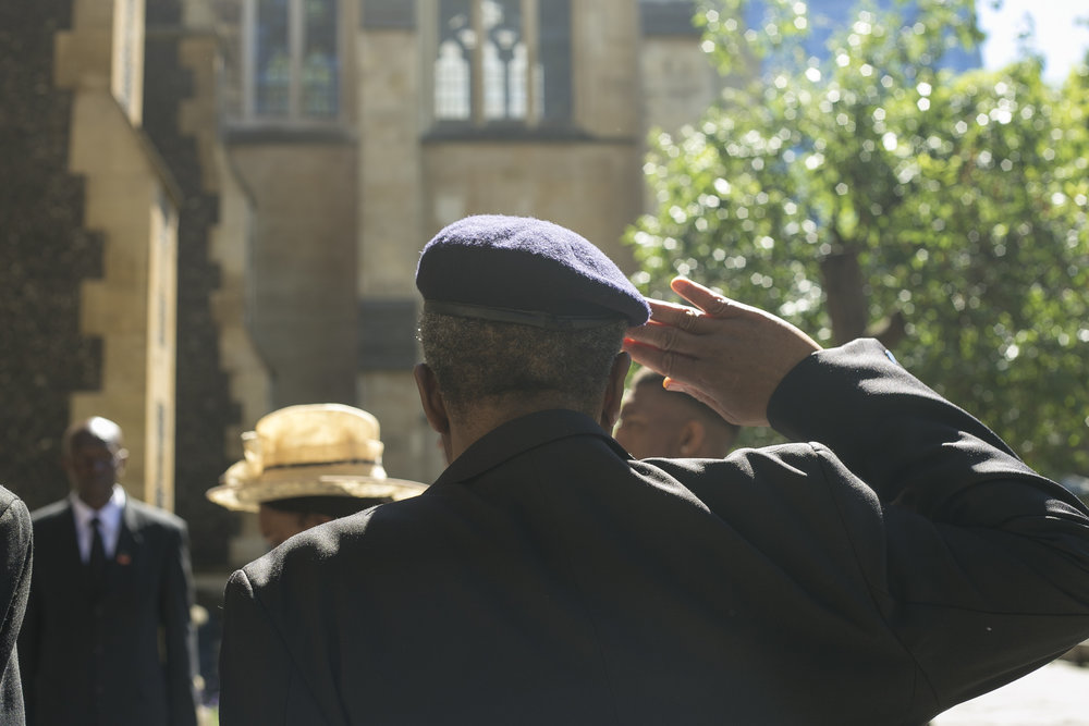 An officer salutes the body of Sam King, the first Black mayor of Southwark council.