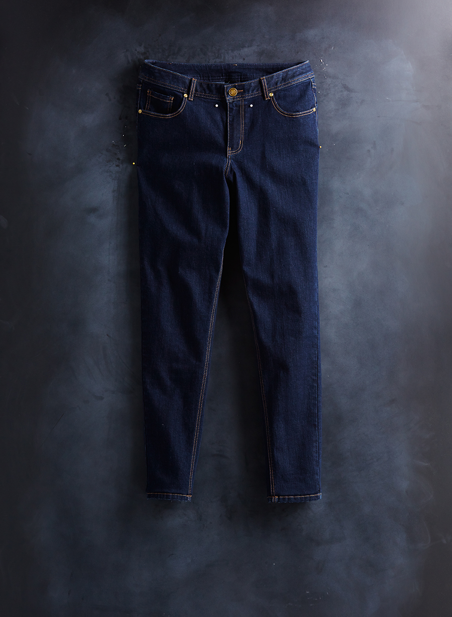 laydown of dark denim jeans  on chalkboard background