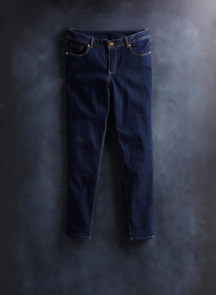 retouched laydown of dark denim jeans on chalkboard background