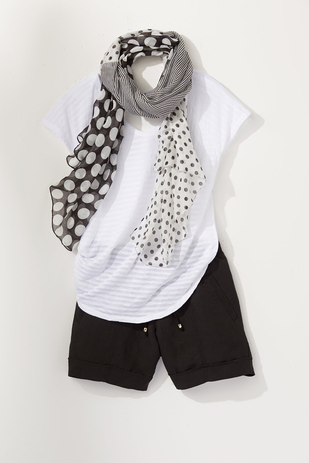 laydown of white t-shirt and black shorts with black and white scarf