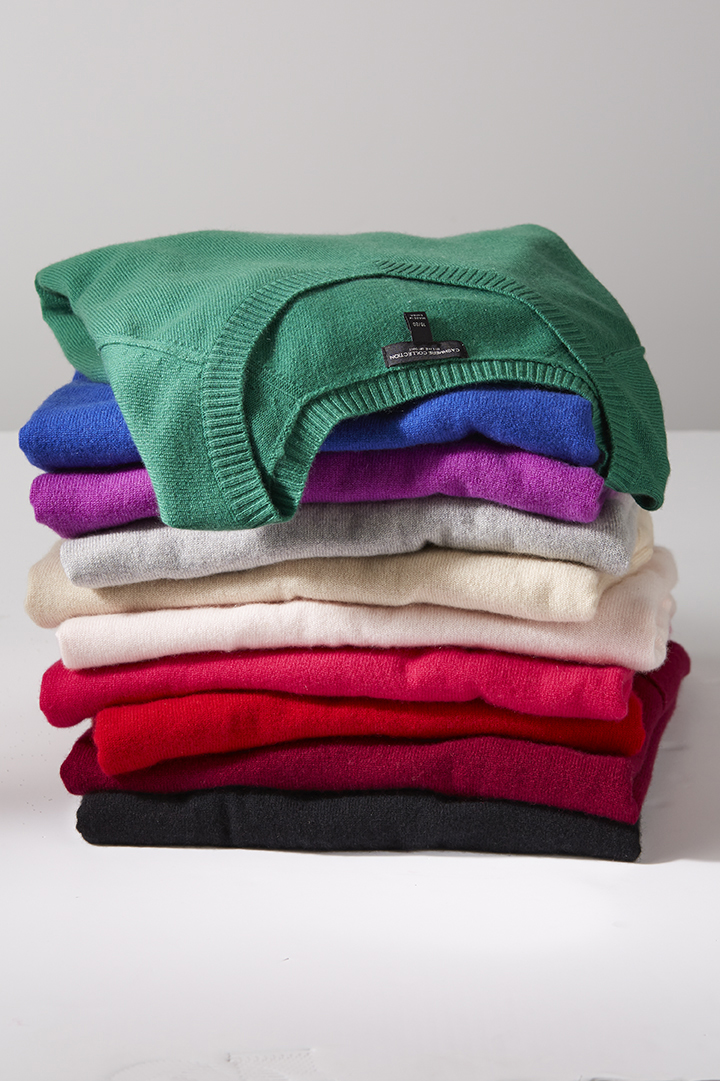 stack of colorful sweaters on white board