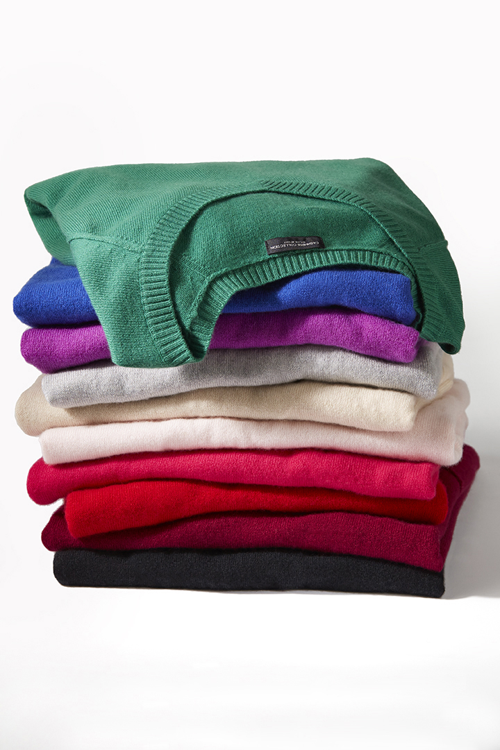 retouched stack of colorful sweaters on white background
