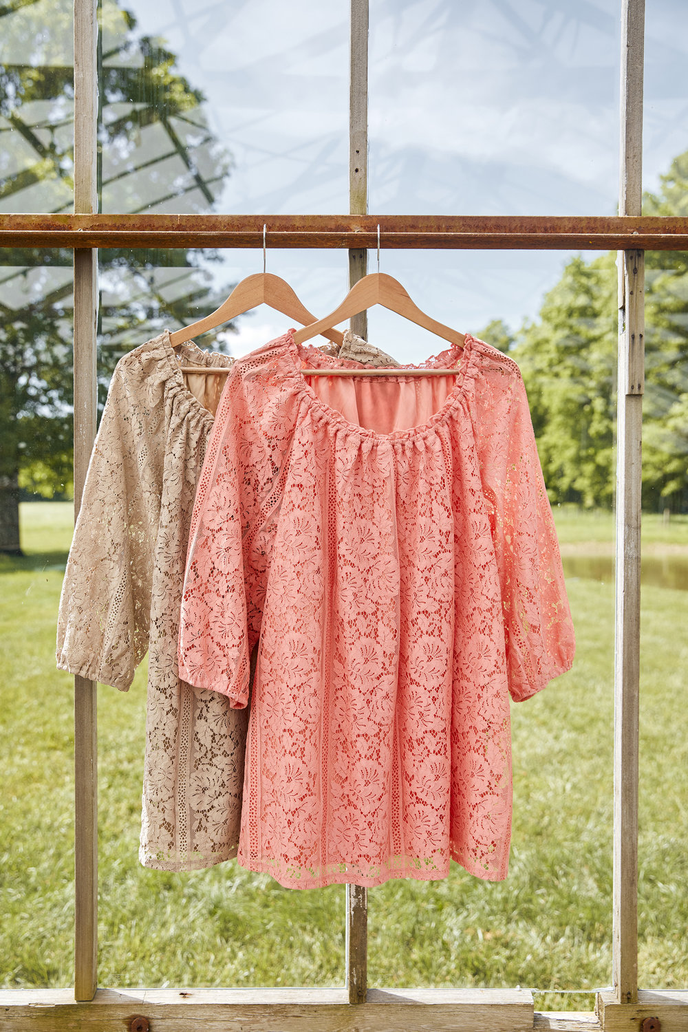 brown and pink lace shirts hanging in window frame on sunny day