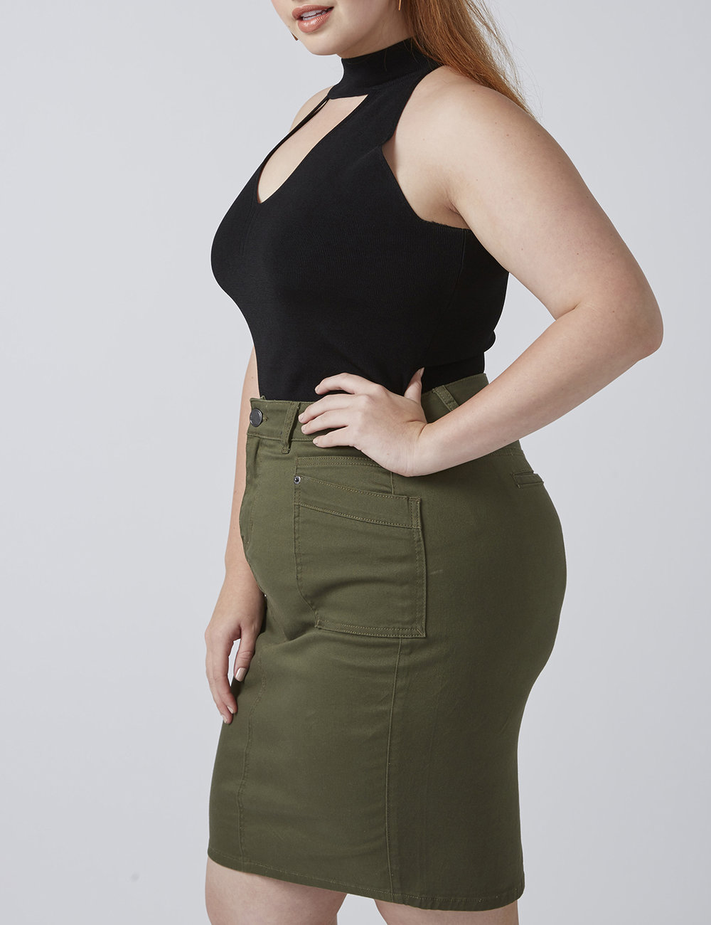 fashion model in black tank top and military green skirt posing with hand on hip