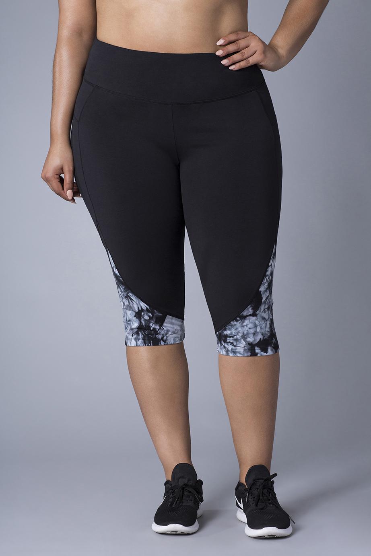 retouched woman, hand on hip, wearing black athletic capri leggings