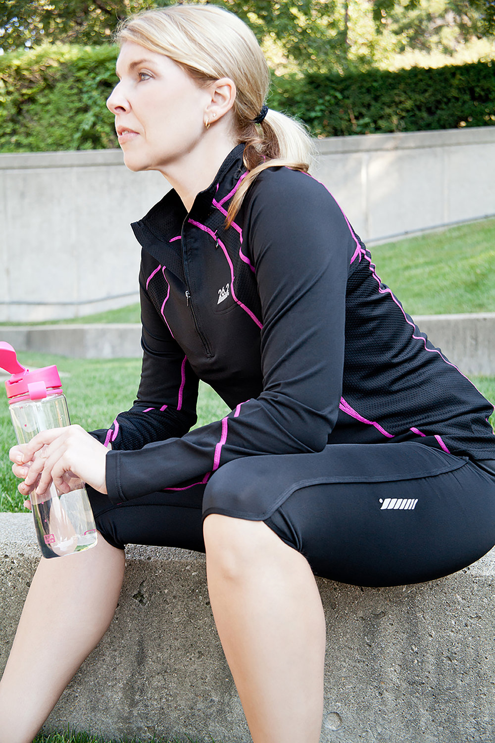 retouched athletic woman sitting in the park holding a water bottle