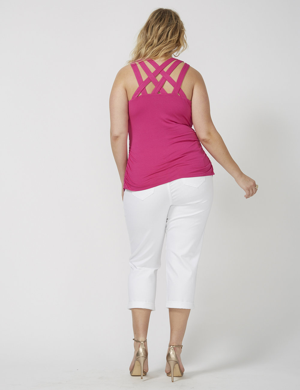 back of fashion model wearing pink tank top and white capris for ecommerce site