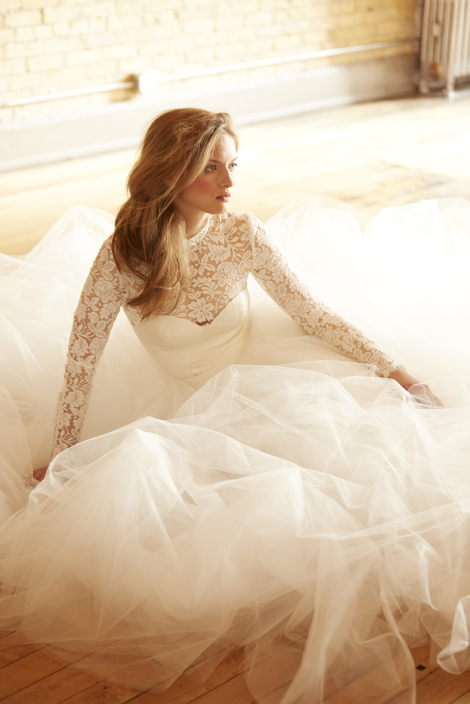 bride sitting on wooden floor in full wedding dress looking contemplative