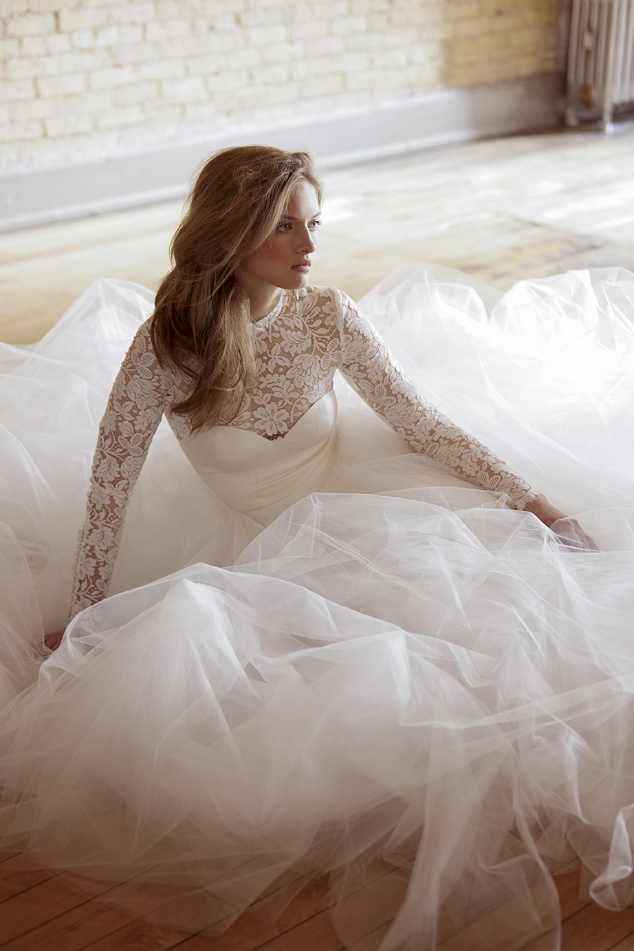 retouched bride sitting on wooden floor in full wedding dress looking contemplative
