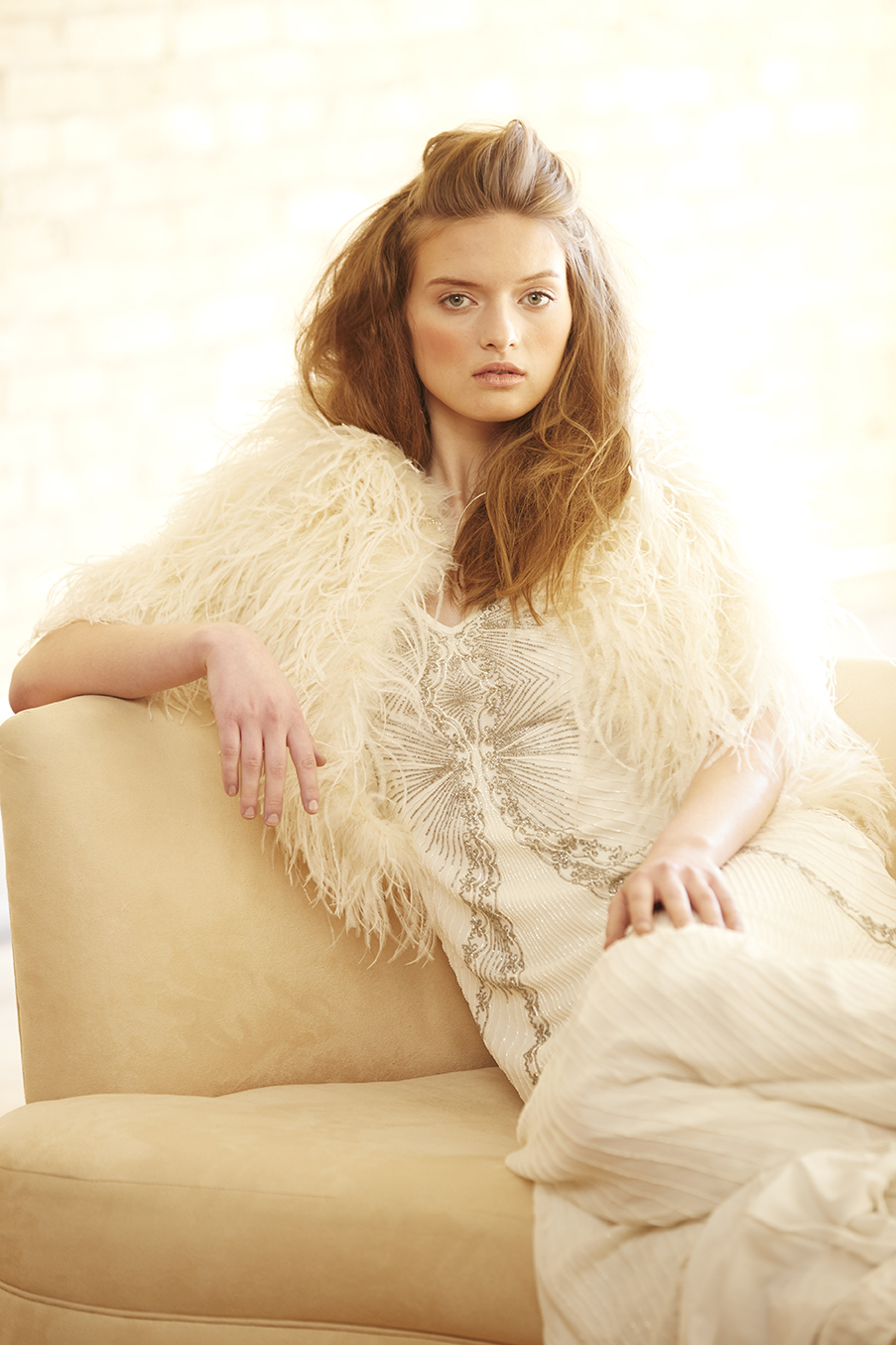 bride resting on sofa in feathered jacket
