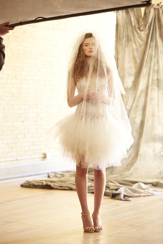 bride standing in studio wearing short tutu wedding dress and veil