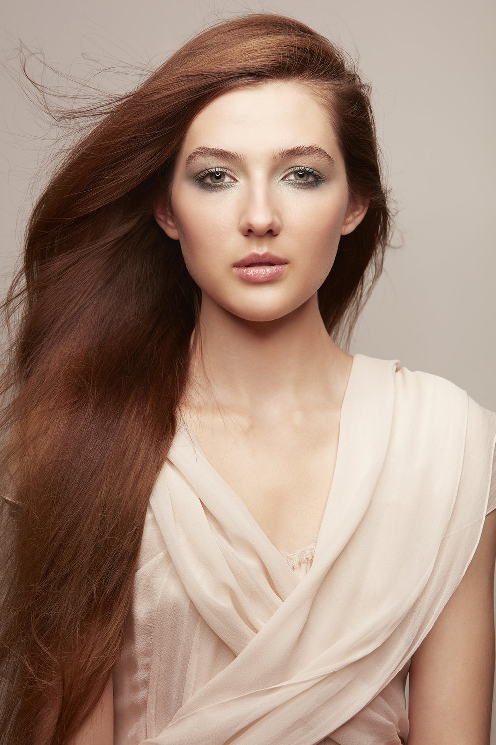 retouched woman in silk wrap with long copper hair blowing in the wind