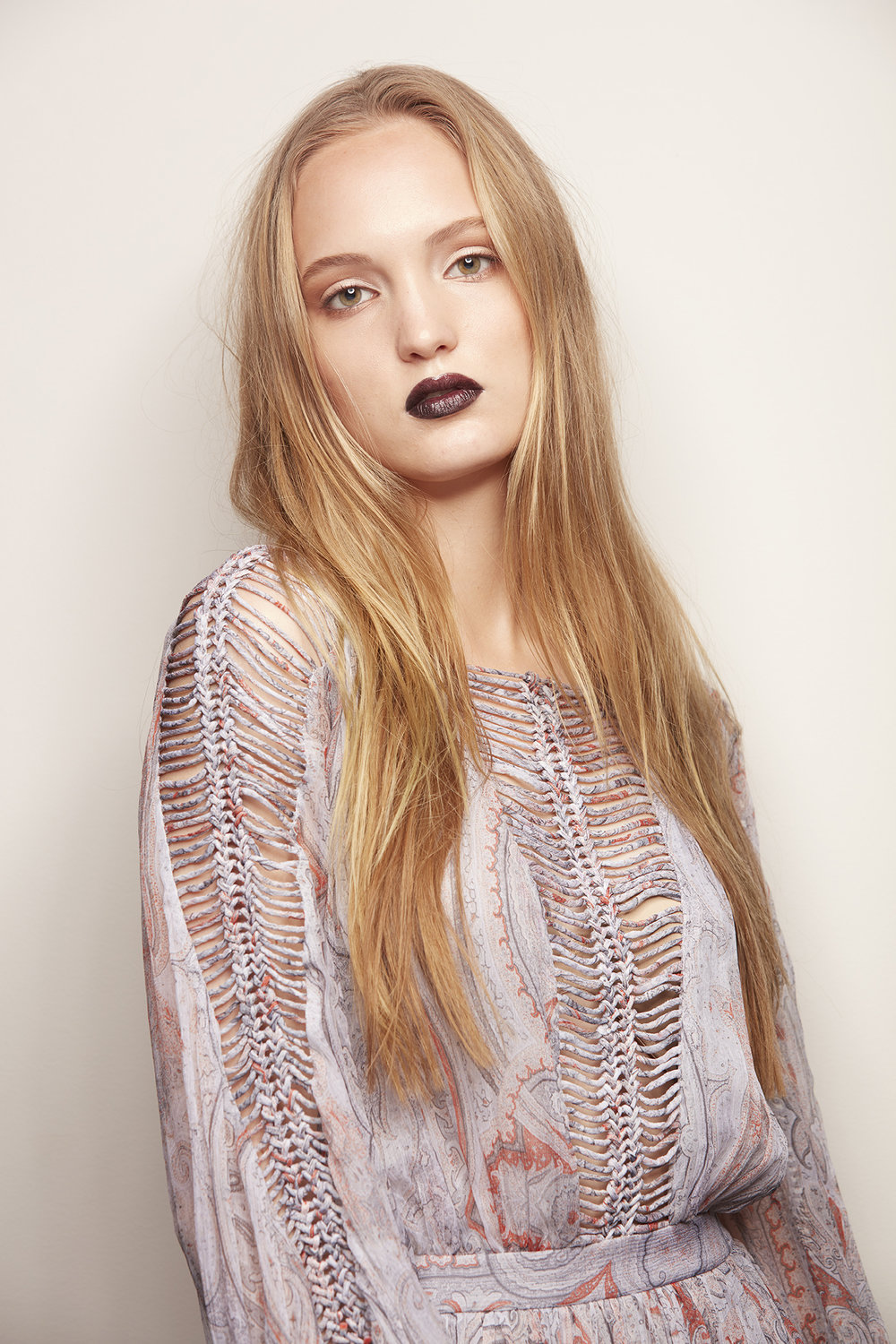 woman with long blonde hair and dark purple lipstick in boho dress