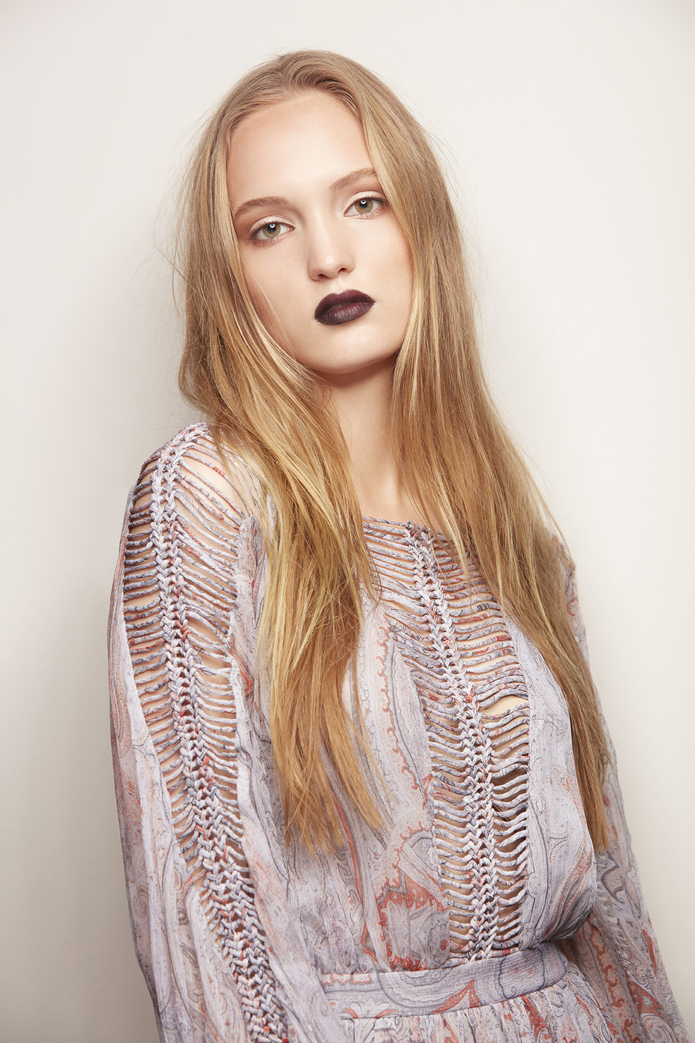 retouched woman with long blonde hair and dark purple lipstick in boho dress