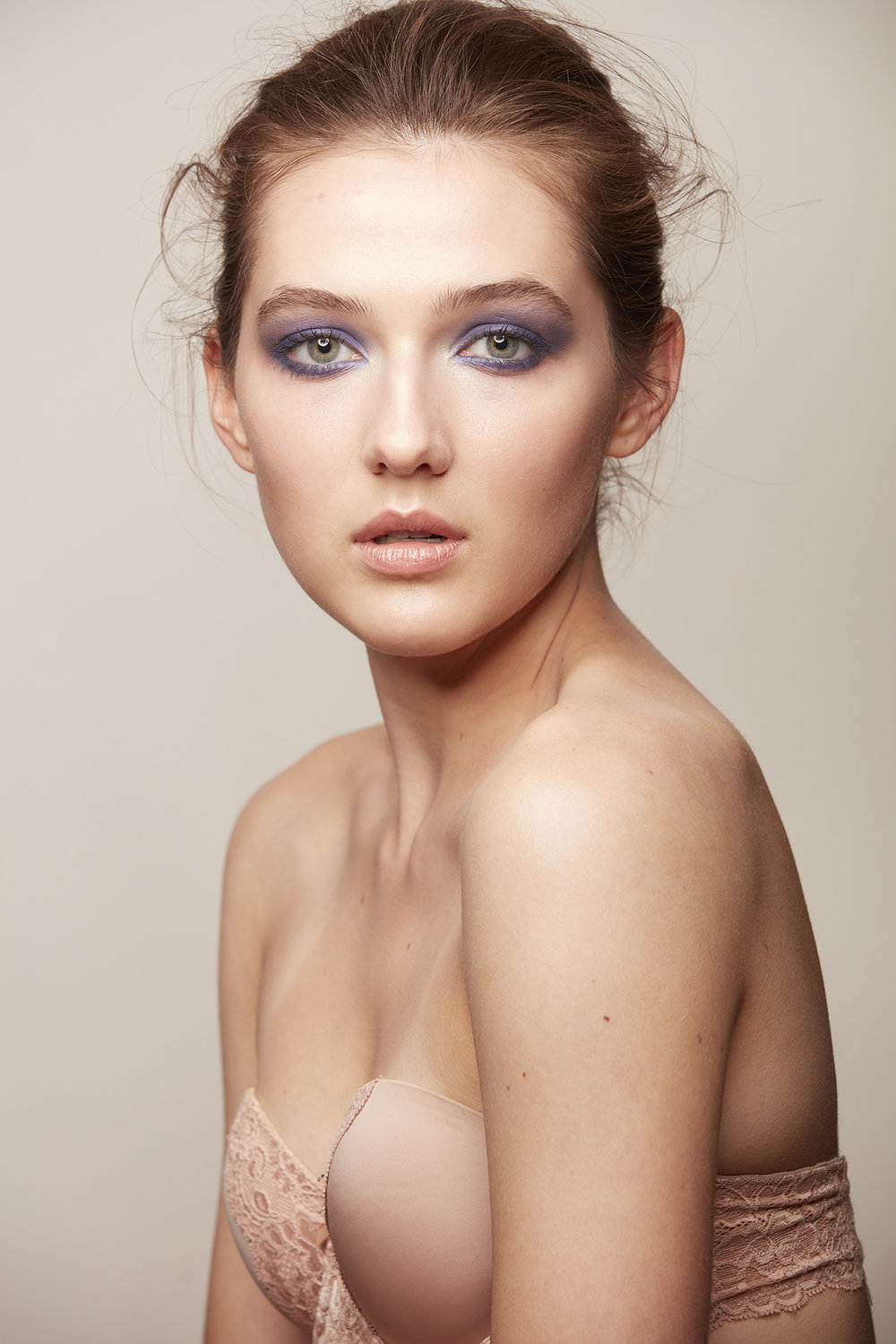 woman with hair up wearing periwinkle eye shadow