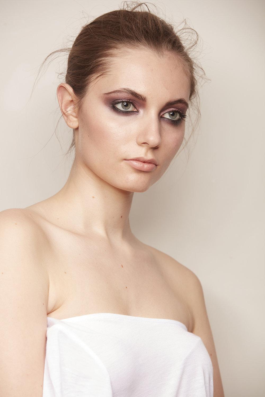woman with hair up wearing dark smoky eyeshadow