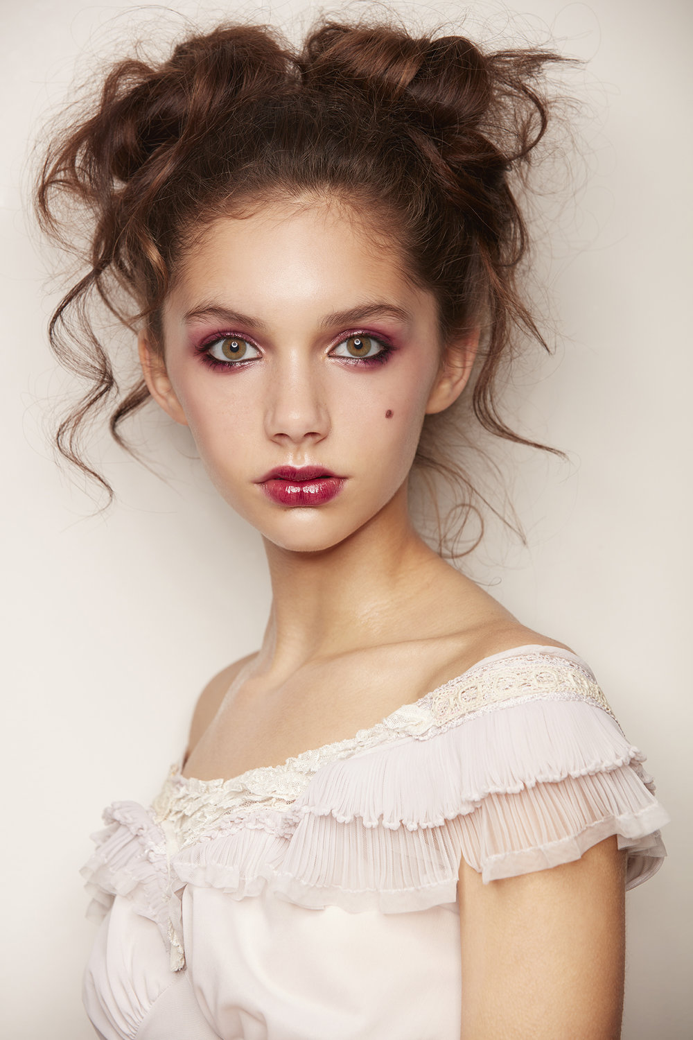 retouched doll-like young woman in lacy dress, hair in buns