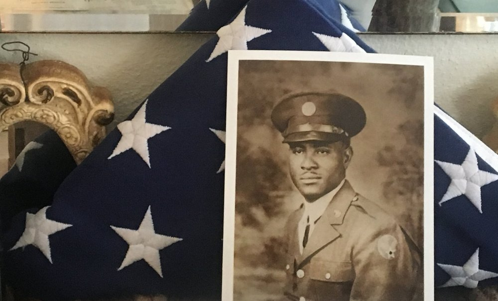 A photo of Richard Overton in his military uniform against a folded American flag.