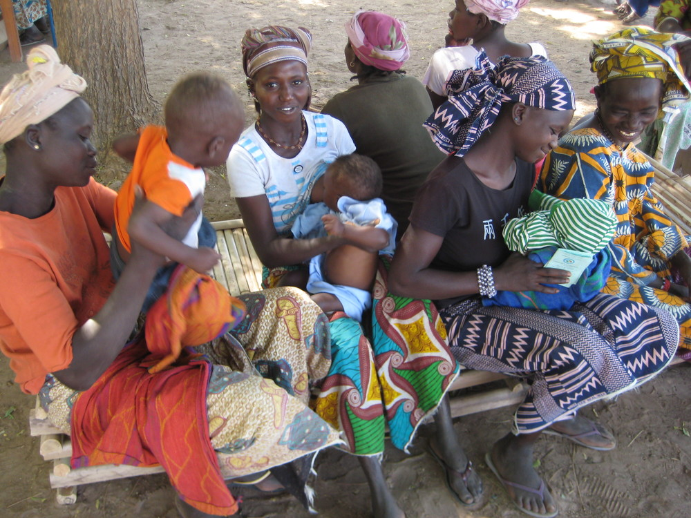 Young mothers and children waiting to get immunizations.