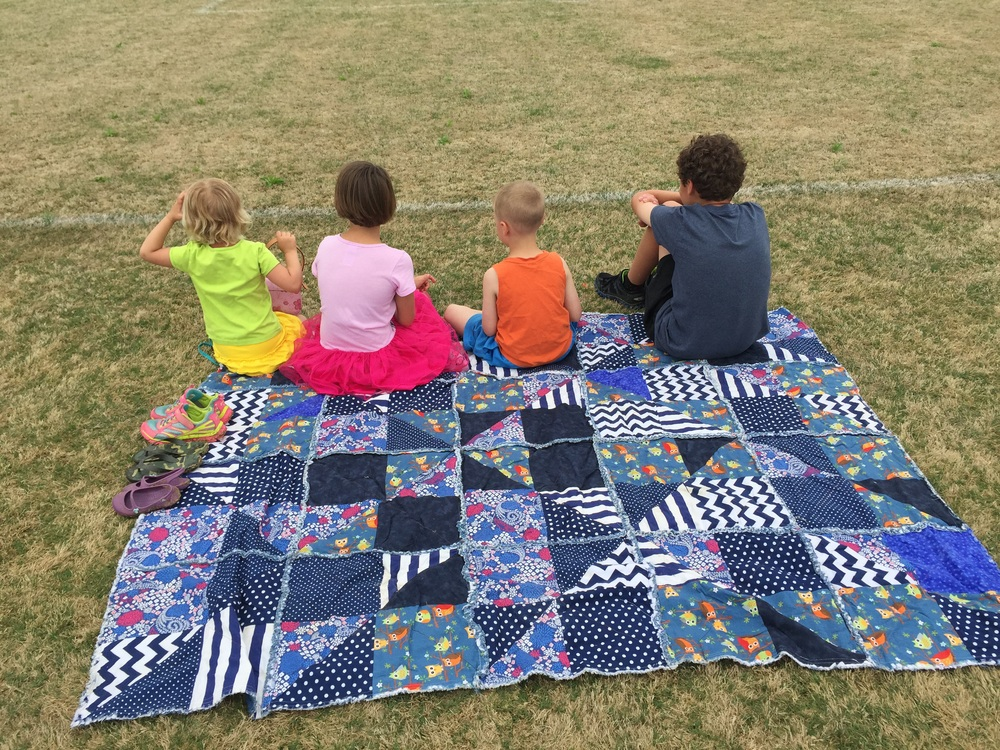 Four of six kids. They are watching their sister play soccer.