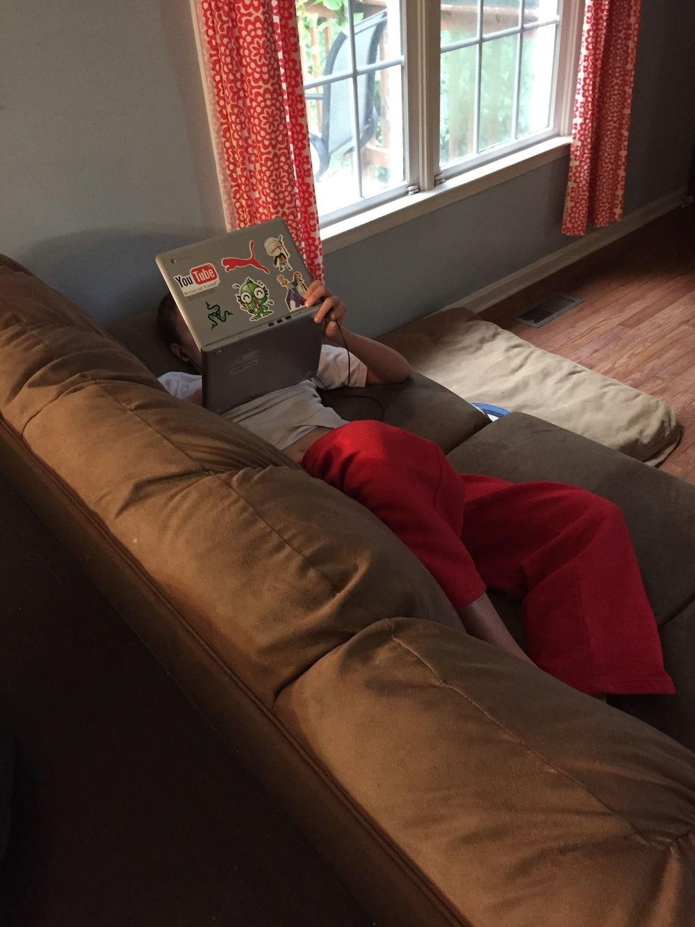 Cameron - working on school, on the couch, in his PJ's! 8th grade isn't so bad.