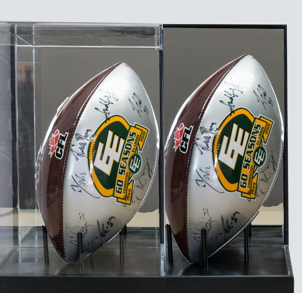 Acrylic box holding autographed Edmonton Eskimo Football